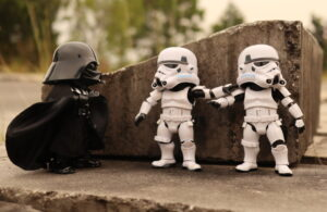 A Darth Vader toy confronting two Storm Trooper toys behind a small piece of concrete