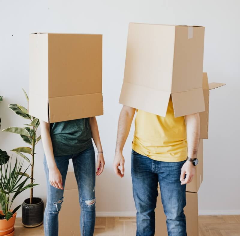Two people with cardboard boxes over their heads standing in a mostly empty room.