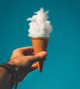 A hand holding an ice cream cone such that its perspective makes a cloud look like ice cream in the cone.
