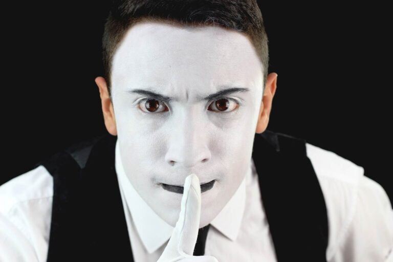 Head and shoulders shot of a mime with a finger held to their lips