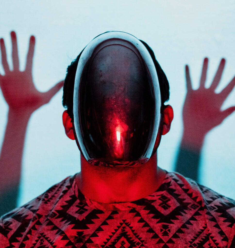 Person with a mirror mask over their face and lit with red light. Two hands are raised behind them.